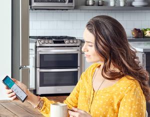 Mujer controlando electrodoméstico conectado